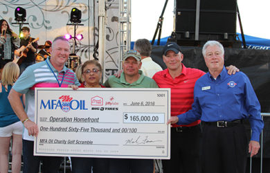 Mark Fenner, MFA Oil president and CEO, presents a $165,000 check to Operation Homefront during MFA Oil's Annual Charity Golf Scramble & Concert.