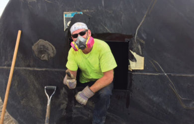 Keller Colley, senior EH&S compliance administrator, cleans out an underground storage fuel tank for disposal. Discarded tanks are frequently sold to scrap yards.